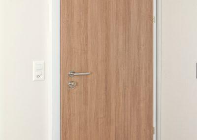 Pose d'une porte palière EI30 (anti-feu) à recouvrement en cerisier
