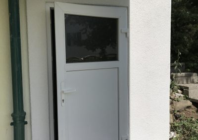 Après la rénovation, pose d'une porte en PVC, d'un panneau isolant en guise de couverte et d'un nouveau crépis.
